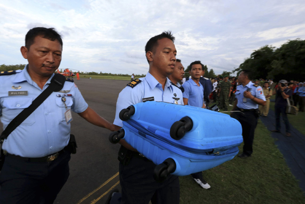 Air force personnel carry luggage presumed to be from missing Indonesia AirAsia flight QZ 8501 recovered from the sea at Pangkalan Bun (Credit: Reuters)