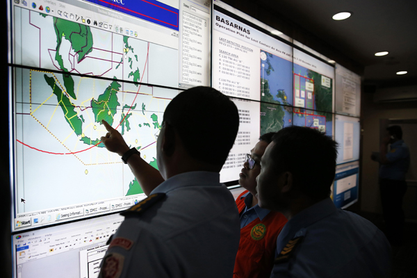 Military and rescue authorities monitor progress in the search for AirAsia Flight QZ8501  inside the National Search and Rescue Agency in Jakarta on Dec 29th, 2014 (Credit: Reuters)