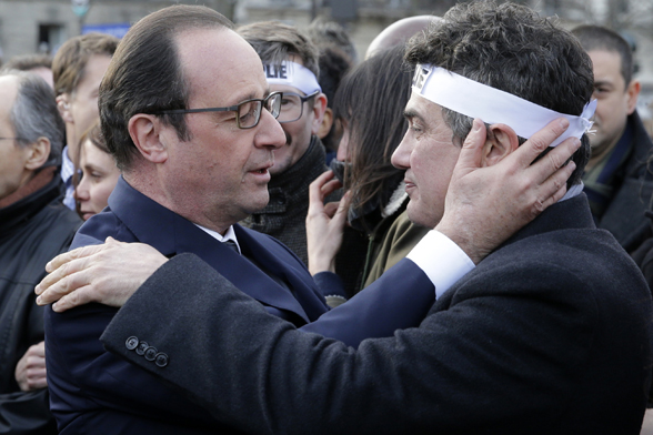 French President Francois Hollande comforts French columnist for Charlie Hebdo Patrick Pelloux as they take part in a solidarity march (Marche Republicaine) in the streets of Paris