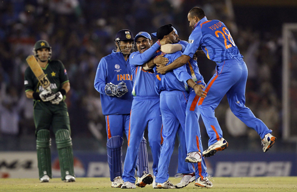 India's Singh is congratulated by teammates after taking wicket of Pakistan's Akmal during their ICC Cricket World Cup 2011 semi-final match in Mohali