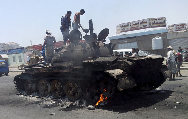 People stand on a tank that was burnt during clashes on a street in Yemen's southern port city of Aden on March 29, 2015. Source: REUTERS