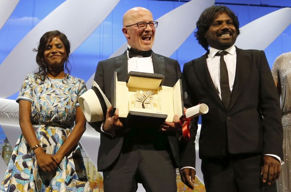 """Director Jacques Audiard (C), Palme d'Or award winner for his film """"Dheepan"""", actress Kalieaswari Srinivasan and actor Jesuthasan Antonythasan pose on stage during the closing ceremony of the 68th Cannes Film Festival."""