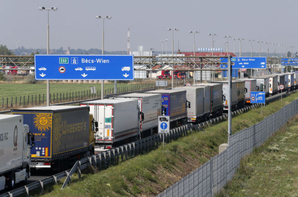 Trucks stand in a queue along a highway near the Austrian border in Hegyeshalom