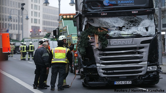 Fire fighters stand beside the truck which ploughed last night into a crowded Christmas market in the German capital Berlin, Germany, December 20, 2016. REUTERS/Hannibal Hanschke - RTX2VSPR