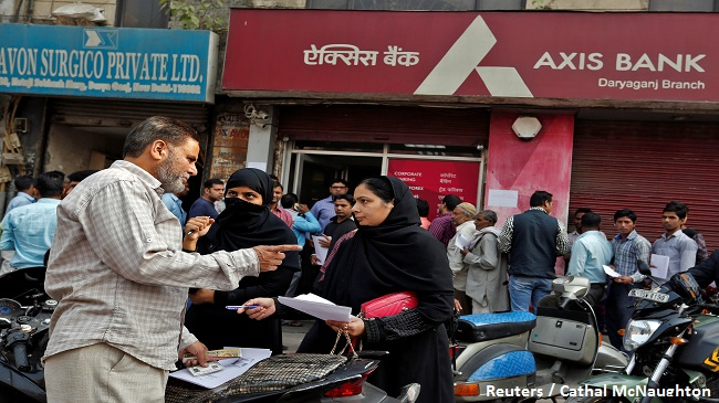 People prepare documents outside a branch of Axis Bank before queueing to exchange old high denomination bank notes in Old Delhi, India, November 10, 2016. REUTERS/Cathal McNaughton - RTX2SY3S