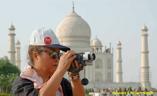 A tourist takes a photograph in front of the Taj Mahal in the tourist city of Agra