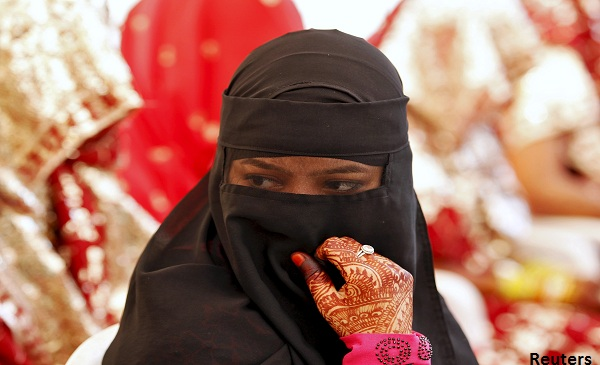 A veiled Muslim bride waits for the start of a mass marriage ceremony in Ahmedabad