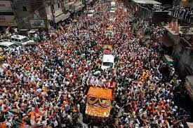 The image shows PM Modi on a truck covered with flowers in the middle of the road with people all around him. It is an old picture of him from a roadshow in Varanasi in 2014 when Narendra Modi had filed his nomination in Varanasi.