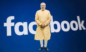 Image shows Modi standing before Fb logo
